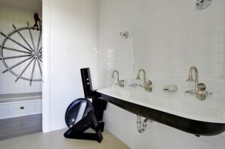 Long, cast iron sink with three faucets.