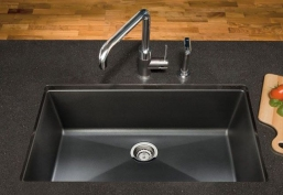 Black composite sink, under-mount with large, single tub. Shown with faucet and sprayer.