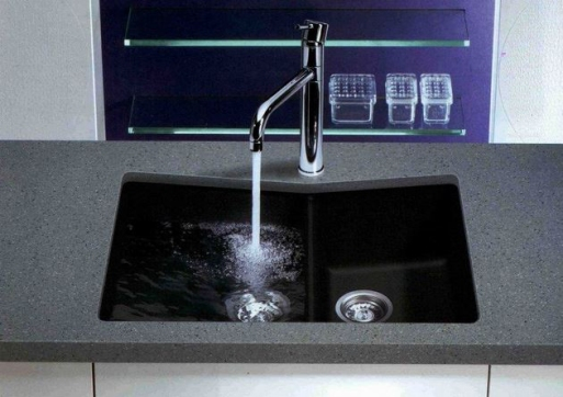 Under-mount composite sink, black and divided into two tubs with tall faucet.