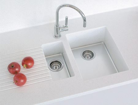 Large tub with shallow small tub and draining board in solid surface.
