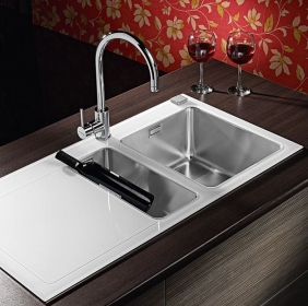 Unequally divided sink with drain board in stainless steel.