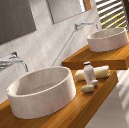 Circular, stone sinks with wall-mounted faucets.