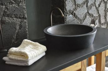 Stone basin sink, top-mounted in bathroom.