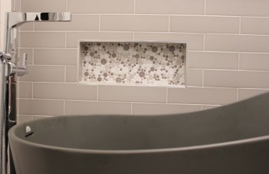 Stand alone graphite tube with standing filler in modern style. Elongated subway tile on surround with bubble-tile niche.