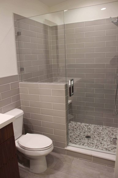 Elongated subway tile with a glass panel and door make this room luxurious. Bubble tile on the shower floor gives it personality.