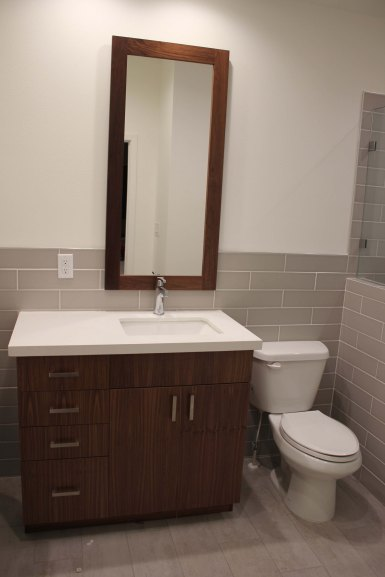 Walnut vanity, quartz countertop, rectangular sink, custom mirror and wood-plank tile flooring.